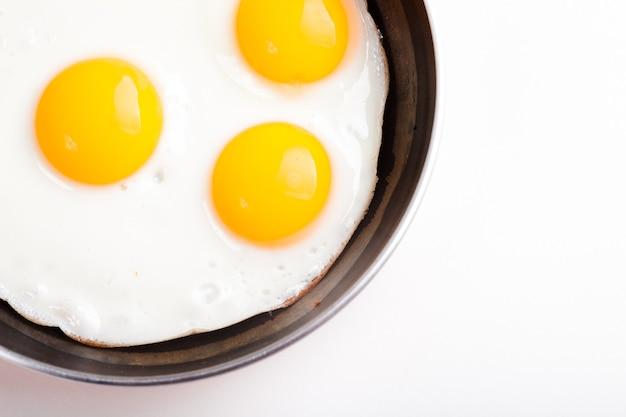Trzy jajka sadzone na patelni teflonowej bez oleju na białym tle