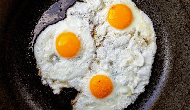 Trzy jajka sadzone z wolnego wybiegu na gorącej patelni nieprzywierającej.