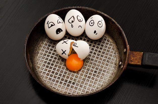 Trzy jajka z emocjami, połamane jajko na środku patelni, czarny stół