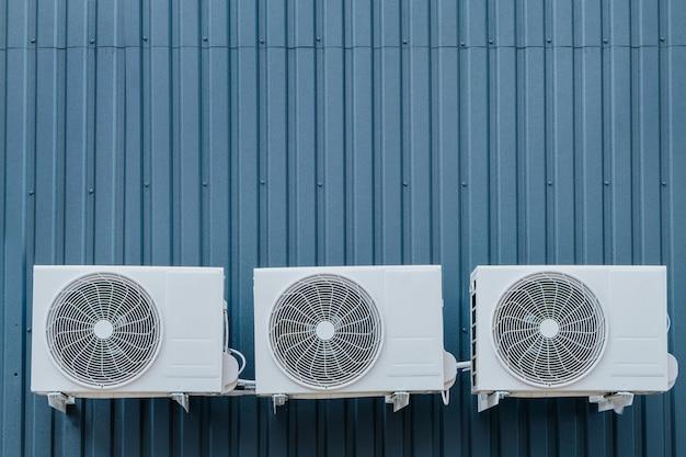 Trzy jednostki zewnętrzne klimatyzatora na niebieskiej ścianie. kopia-przestrzeń.