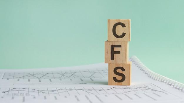 Trzy kamienne kostki na tle białych sprawozdań finansowych, tabele z napisem cfs - akronim skonsolidowane sprawozdanie finansowe. silna koncepcja biznesowa. szare tło.
