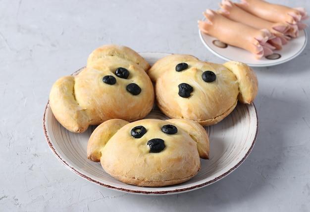 Trzy kanapki w kształcie psa z kiełbasą na jasnoszarym tle. pomysł na gotowanie dla dzieci. zbliżenie