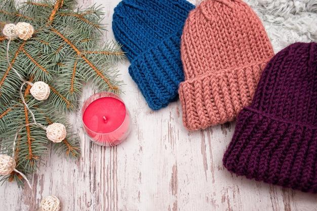 Trzy kapelusze. niebieski, koralowy i fioletowy. świerkowa gałąź, girlanda i świeca. drewniane tło. koncepcja noworoczna.
