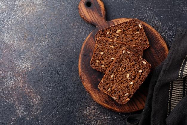 Trzy kawałki chleba żytniego z pestkami słonecznika na kanapki na stojaku