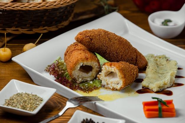 Trzy kawałki kurczaka kijowego z puree podane w białym talerzu