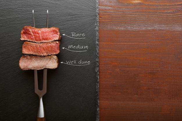 Trzy kawałki mięsa na widelcu do mięsa. trzy rodzaje pieczenia mięsa, rzadkie, średnie, dobrze zrobione.