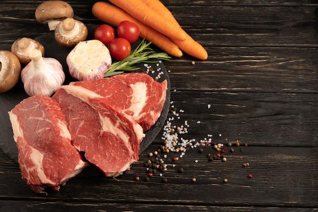 Trzy kawałki soczystej surowej wołowiny z warzywami na kamiennej desce do krojenia na czarnym drewnianym stole.