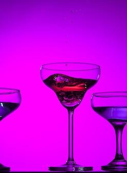 Trzy kieliszki do wina nadziewane stojące na stole w studio. żywe, jasne, kolorowe oświetlenie. modna w 2018 roku żarówka ultrafioletowa. dekoracja artystyczna z odcieniem mistycznego koloru