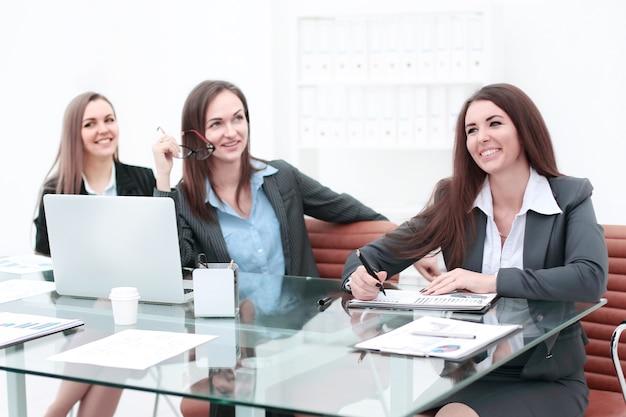 Trzy kobiety biznesu spotykają się przy stole w nowoczesnym biurze