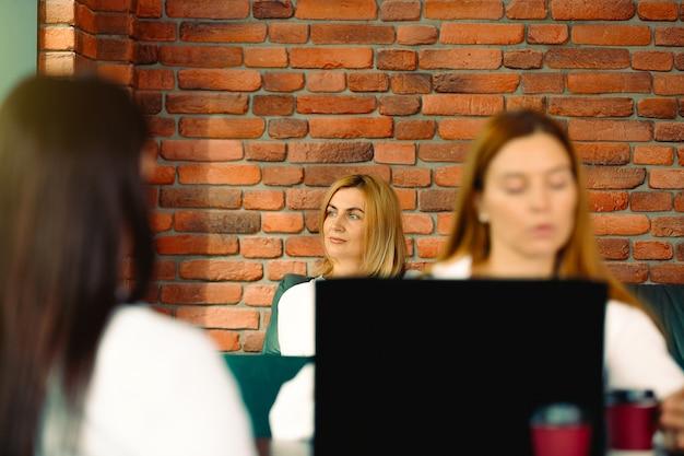 Trzy kobiety biznesu stojące naprzeciw siebie w miejscu pracy wnętrza nowoczesnego industrialnego ceglanego loftu. skoncentruj się na liderze zespołu. czekam na rozmowę, marząc o udanej pracy.