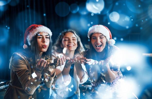 Trzy kobiety dmuchające konfetti z rąk w pomieszczeniu w czasie wakacji.