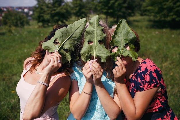 Trzy kobiety, których twarze są ukryte za ogromnymi liśćmi łopianu