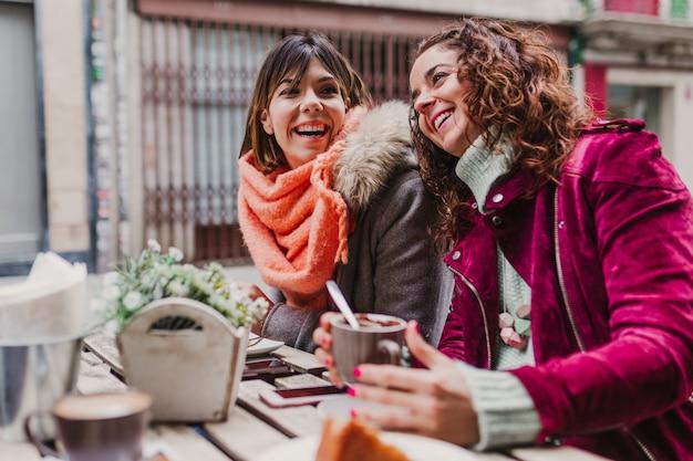 Trzy kobiety przyjaciela ma kawę w tarasie w oporto, portugalia. zabawna rozmowa