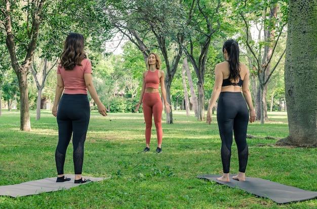 Trzy kobiety robi joga w parku