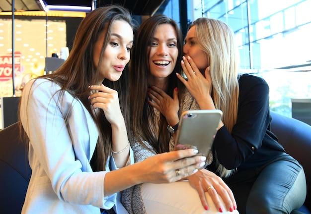 Trzy kobiety robiące selfie podczas zakupów w sklepie odzieżowym. są szczęśliwi i uśmiechają się do kamery. koncepcja zakupów, również związana z uzależnieniem od mediów społecznościowych