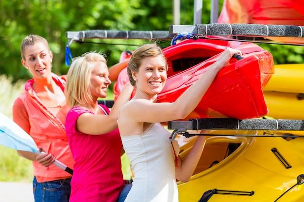 Trzy kobiety rozładowujące kajak z przyczepy łodzi