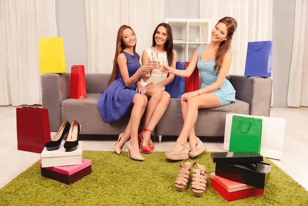 Trzy kobiety świętują udane zakupy i brzęczą kieliszkami szampana