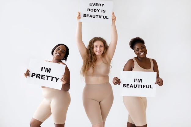 Trzy kobiety trzymające plakaty z informacją o pozytywnym nastawieniu do ciała