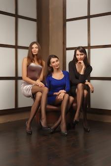 Trzy kobiety w dopasowanej sukience w fotelu. pozowanie przyjaciół.