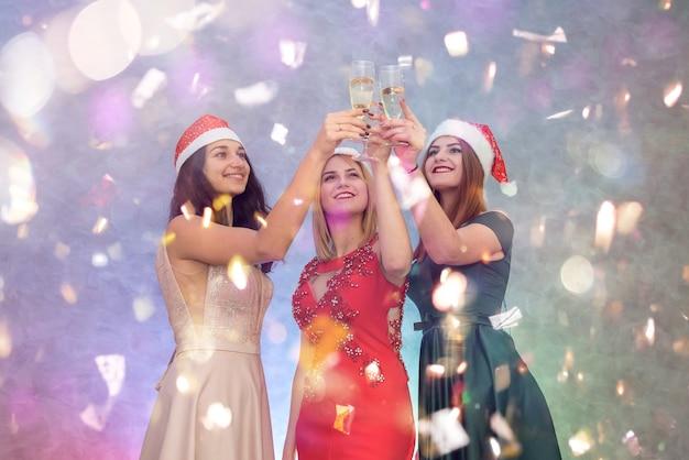 Trzy kobiety w eleganckich sukienkach i czapkach mikołaja z kieliszkami szampana. koncepcja wesołych świąt.