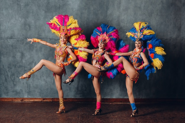Trzy kobiety w stroju kabaretowym z kolorowym upierzeniem