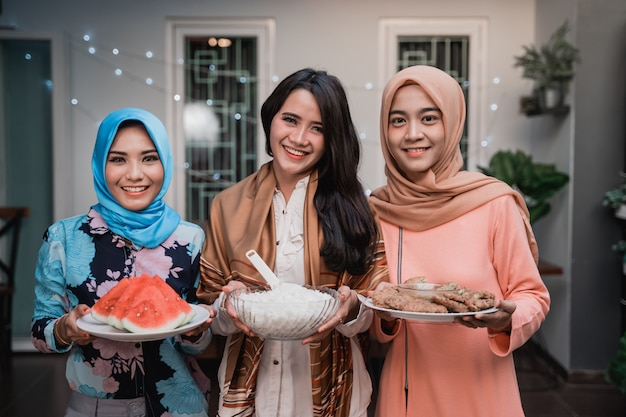 Trzy kobiety z hidżabu przygotowujące jedzenie do podania podczas szybkiego zerwania