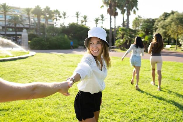 Trzy koleżanki biegają szczęśliwie w zielonym ogrodzie - piękna blondynka wyciąga rękę innej, by wspólnie cieszyć się dwiema młodymi kobietami na łonie natury
