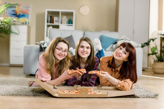Trzy koleżanki jedzące pizzę na przyjęciu w domu, leżąc na podłodze w przytulnym pokoju
