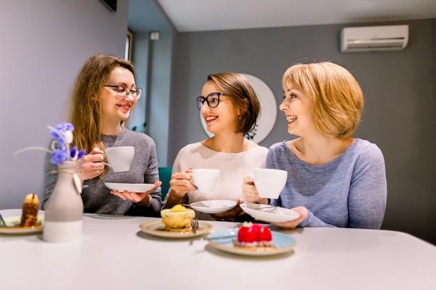 Trzy koleżanki piją kawę i jedzą desery ciasta w kawiarni w pomieszczeniu