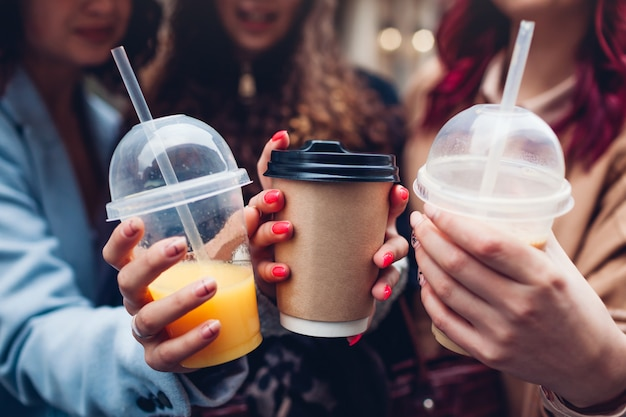 Trzy koleżanki posiadające napoje na zewnątrz. szczęśliwe kobiety brzęczą filiżankami kawy, soku pomarańczowego i herbaty