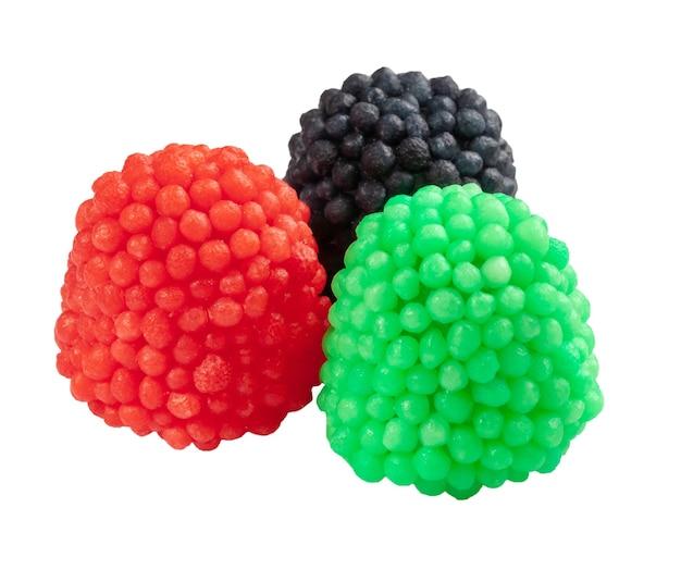 Trzy kolorowe gumowate cukierki w kształcie malin na białym tle