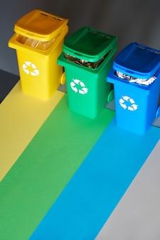 Trzy kolorowe kosze do recyklingu, izometryczny obraz na geometrycznym tle warstwowego papieru.