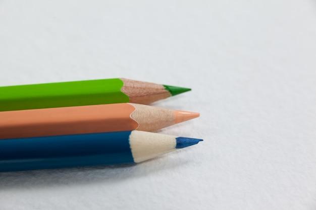 Trzy kolorowe kredki na białym tle