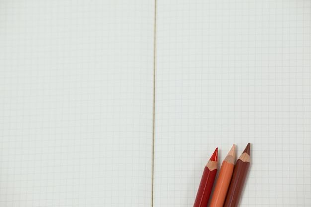Trzy kolorowe kredki trzymane w notesie