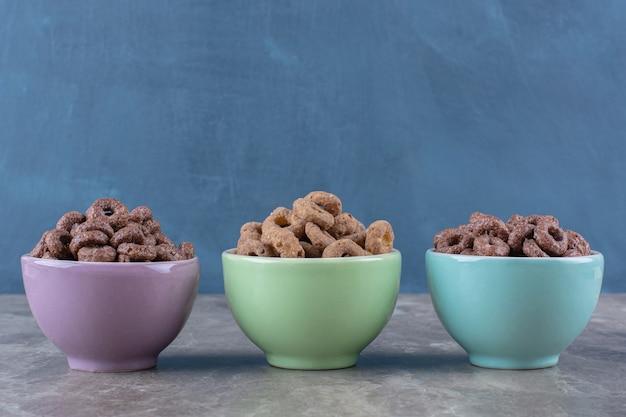 Trzy kolorowe miseczki czekoladowych krążków zbożowych na śniadanie.