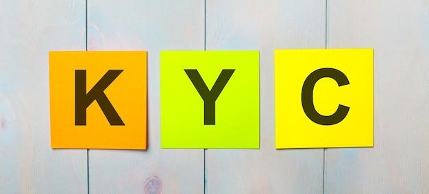 Trzy kolorowe naklejki z napisem kyc know your customer na jasnoniebieskim drewnianym tle