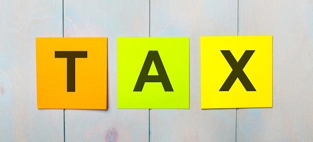 Trzy kolorowe naklejki z napisem tax na jasnoniebieskim drewnianym tle