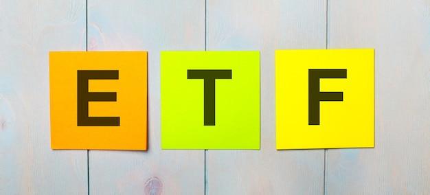 Trzy kolorowe naklejki z tekstem etf exchange traded funds na jasnoniebieskim drewnianym tle