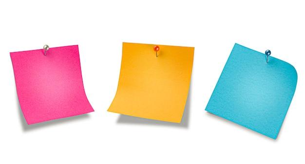 Trzy kolorowe notatki na szpilkach. na izolowanej powierzchni