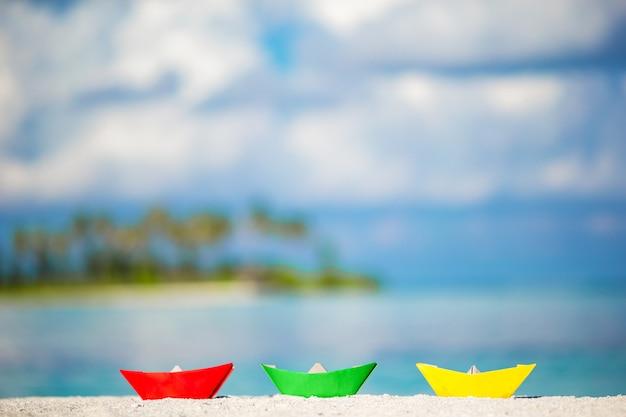 Trzy kolorowe papierowe łódki na turkusowym oceanie.