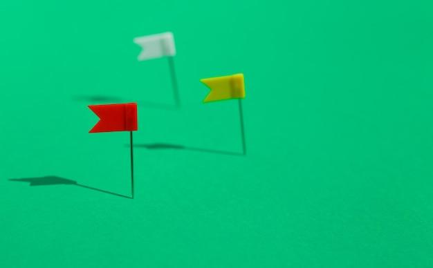 Trzy kolorowe szpilki małe flagi przypięte na zielonej powierzchni. koncepcja biznesowa lub podróżnicza. cele .