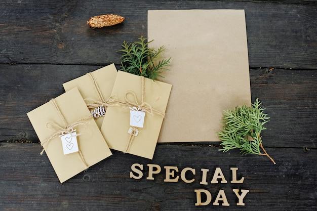 """Trzy koperty rzemieślnicze i kawałek papieru rzemieślniczego. miejsce na twój tekst i wiadomość. ręcznie robione opakowanie na prezent. napis jest napisem """"dzień specjalny""""."""