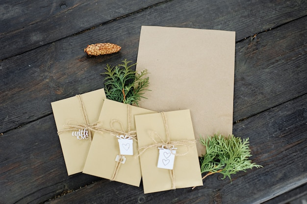 Trzy koperty rzemieślnicze i kawałek papieru rzemieślniczego. miejsce na twój tekst i wiadomość. ręcznie robione opakowanie na prezent.