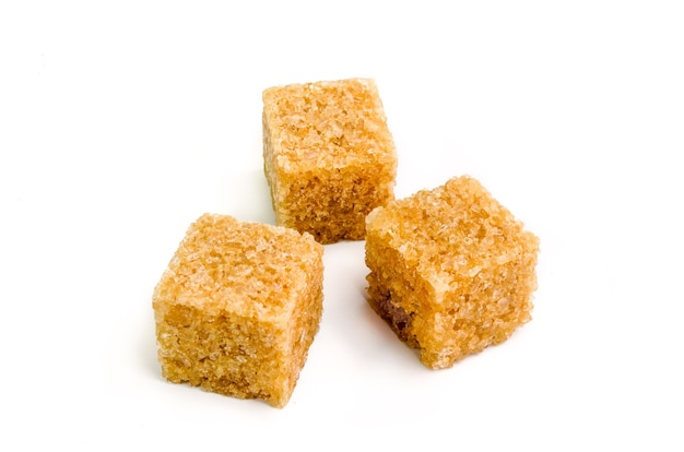 Trzy kostki brązowego cukru z cieniem na białym tle.