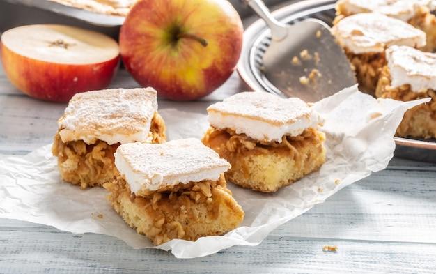 Trzy kostki szarlotki z ubitym białym wgg polewą na serwetce z większą ilością ciasta i świeżymi jabłkami z tyłu.