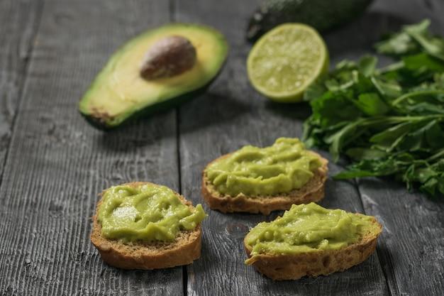 Trzy kromki chleba z guacamole na czarnym drewnianym stole. dieta wegetariańska meksykańskie jedzenie awokado. surowe jedzenie.