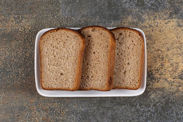 Trzy kromki czarnego chleba na białym kwadratowym talerzu.
