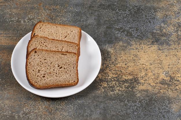 Trzy kromki czarnego chleba na białym talerzu.