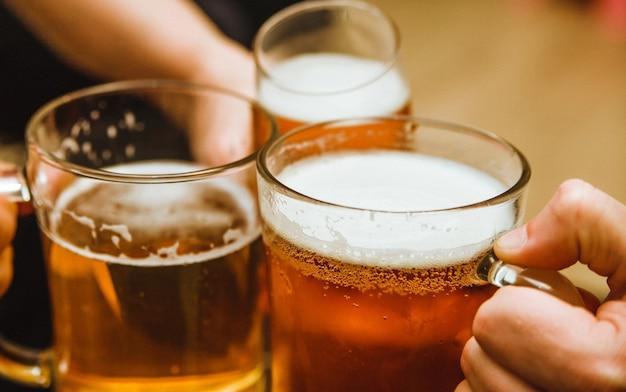Trzy kufle piwa. napój alkoholowy z pszenicy. piękna piana i bąbelki na piwie.