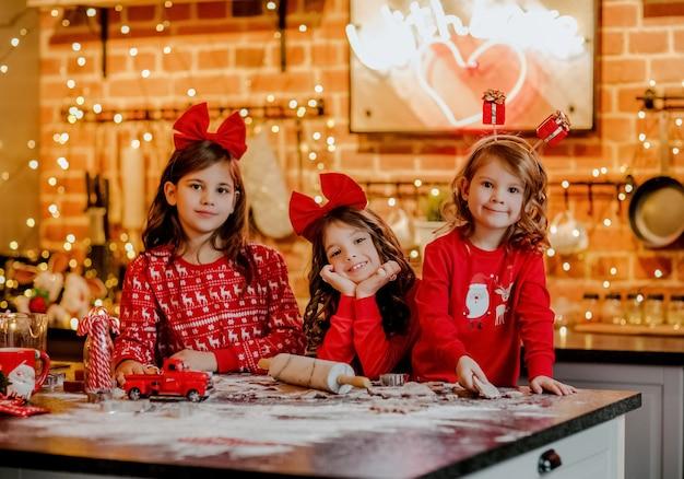 Trzy ładne młode dziewczyny w czerwonej świątecznej piżamie i opaskach na głowie robi ciasteczka w kuchni z tłem bożego narodzenia.
